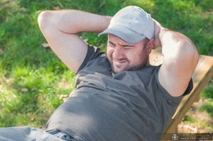 Young Man With Excess Weight Doing Exercises And Rocking His Press In The Park